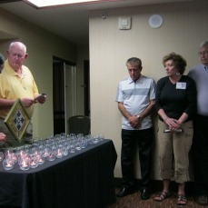 Capt. Konnerman lighting a candle while Sam, Claudia and Chuck look on.