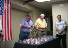 Elmer lighting a candle while Bud and Sam look on