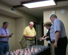 Claudia lighting a candle for Bill Zimmerman while Chuck looks on