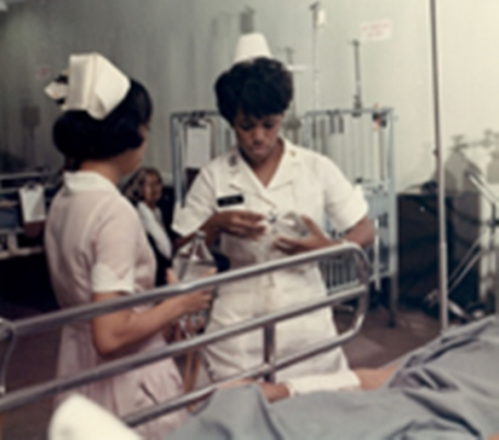 APS-71-796 Vietnam. The Army Nurse in Vietnam. Cpt. Theora L. Peyton (Arlington, VA), changes an intravenous saline bottle on a patient at the 3rd Field Hospital. 12 July 1971. Photo by SP5 Logan McMinn, USA Sp Photo Det, Pac, fn